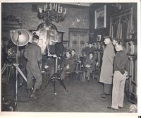 Rear shot of Charles D. Gould, Jr. standing beside a mounted camera in front of a group