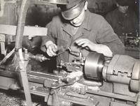 Photograph of unidentified man operating lathe