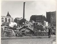 Photo of rubble surrounded by four buildings that are (more or less) intact