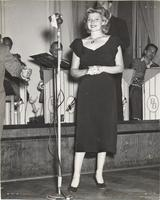 Photo of Rita Hayworth next to a microphone, with members of the Blue Band in the background
