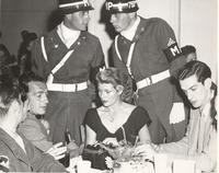 Photo of Rita Hayworth with MPs and other military and civilian personnel