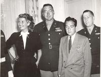 Photo of Rita Hayworth with military and civilian personnel