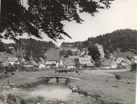 Photo of footbridge over stream, with village in background