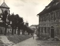 Photo of woman walking down village street