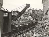 Photo of steam shovel clearing rubble in a town