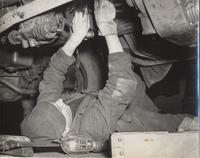 Photo of mechanic working on the under side of a vehicle