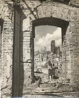 Photo shot through window-shaped opening in dilapidated building, framing view of town or village in rubble