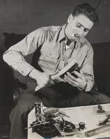 Photo of man using brush on piece of disassembled camera