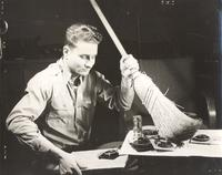 Photo of man sweeping up camera pieces