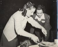Photo of two service women slicing and plating roast turkey