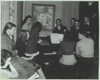 People gathered around a piano