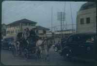 Hiller 09-016: Horse carriage and cars on street in Nanking