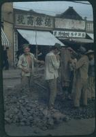 Hiller 09-022: Men working on breaking stones on shop-lined street