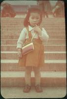 Hiller 09-039: A young girl with a purse standing on steps