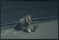 Hiller 04-009: A man, squatting on the ground, begging