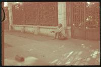 Hiller 04-012: Man with shaved head, white shirt, and outstretched hands, sitting on the sidewalk against a fence