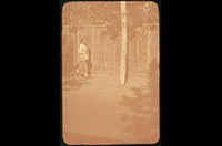 Hiller 04-015: Person with hat walking along a wooden wall