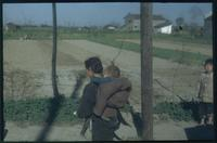 Hiller 04-people-01: A woman carrying an infant on her back, in the countryside