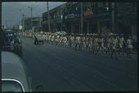 Hiller 04-people-04: Parade of people in uniform, down a street lined with storefronts and power lines