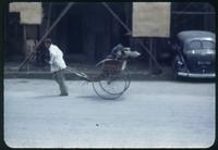 Hiller 08-025: Man pulling a rickshaw cart on foot down the street