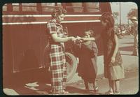 Hiller 08-028: Caucasian woman handing a paper item to two Chinese children