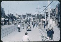 Hiller 08-011: Busy street with a streetcar and decorative archway, Peiping