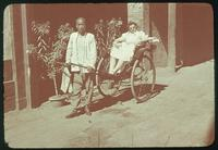 Hiller 08-012: Woman in a rickshaw cart being carried by a man, Peiping
