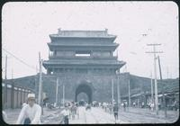 Hiller 08-106: Stone bridge with a building above a busy street, Peiping