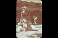 Hiller 08-124: Caucasian woman leaning against a metal dragon statue, Peiping