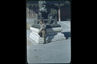 Hiller 08-125: Man wearing green uniform leaning against a metal dragon statue, Peiping
