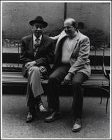 Buck Clayton seated on a bench with a fan
