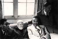 Dizzy Gillespie, Bud Freeman, Buck Clayton, and Gerald Lascelles cozy on a couch