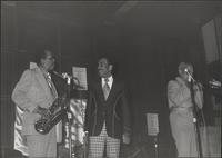 Buddy Tate on stage talking to Buck Clayton while Dicky Wells warms up
