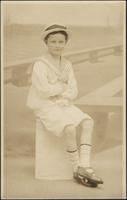 Young boy sitting on a box before a seaside backdrop