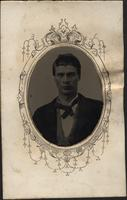Young man in oval frame wearing dark coat, vest, and necktie