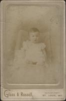 Young child in light dress seated in chair