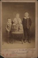 Two boys posed next to a girl on a chair