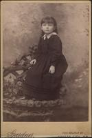Girl seated on arm of wooden chair