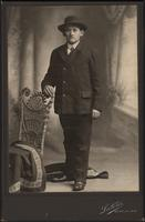 Man standing with his right hand on wicker chair