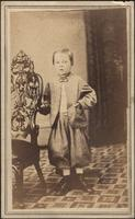 Young boy standing with left hand in jacket pocket