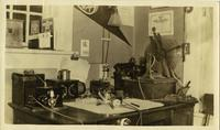Desk with radio equipment in room corner of in front of window books and letters