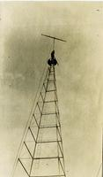 Radio tower with man near top by antenna at Graceland College, Lamoni, Iowa