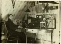 Young man at desk in attic room with radio equipment