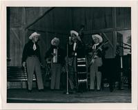 Five piece band performing on stage with barn backdrop