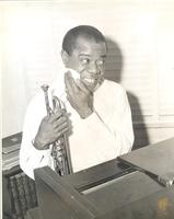 Louis Armstrong sitting at the piano