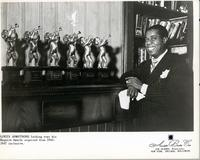 Louis Armstrong looking over his Esquire Awards acquired from 1942-1947 inclusive