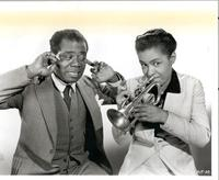 Louis Armstrong covering ears while unidentified woman plays trumpet
