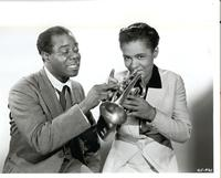 Louis Armstrong showing unidentified woman how to play trumpet