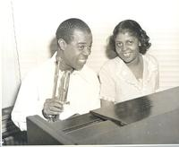 Louis Armstrong and unidentified woman at piano