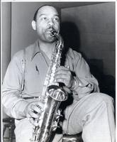 Benny Carter sitting and playing saxophone